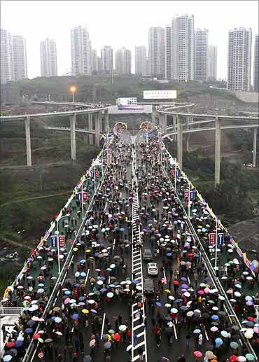 People walk on the Caiyuanba Yangtze River Bridge, in Chongqing municipality.