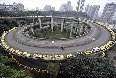 Taxis line up to get their tanks filled on a ramp in Chongqing municipality