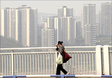 A pedestrian walks on a bridge as residential blocks are seen in the background in Chongqing.