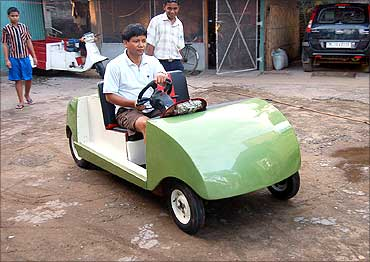 Kanak Gogoi in a car that runs on compressed air. His other innovations include a flying car, a hybrid car, etc.