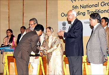 Kanak Gogoi receives an award from President Pratibha Patil.