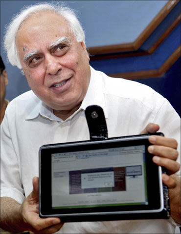 HRD Minister Kapil Sibal displays the low-cost computing device during its unveiling in New Delhi.
