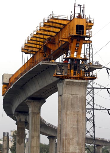 Delhi Metro Rail Corporation employees work at the construction of a flyover in New Delhi.