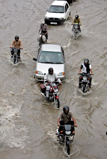 Traffic moves along a flooded road after monsoon rains in New Delhi.