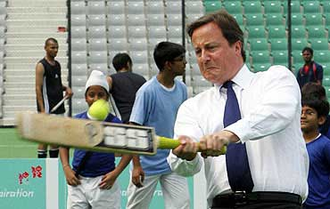 Cameron plays cricket inside a stadium in New Delhi.