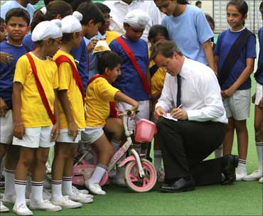 Cameron (C) signs autographs for children inside a stadium.