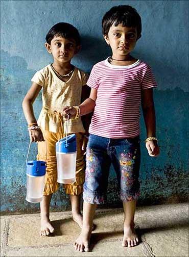 Children holding the Kiran lamp in India.