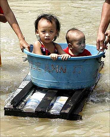 Children ride on a makeshift raft on a flooded road in central Dagupan city in northern Philippines.
