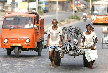 Labourers pull a handcart loaded with iron rods to a road construction site in Kolkata.