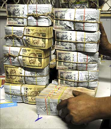 An employee counts bundles of Indian currency notes inside a bank in Agartala.