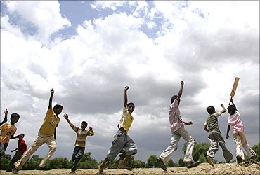 Children play as the monsoon clouds cover the sky in Ahmedabad.