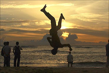A boy somersaults on a beach against the backdrop of monsoon clouds in Kochi.