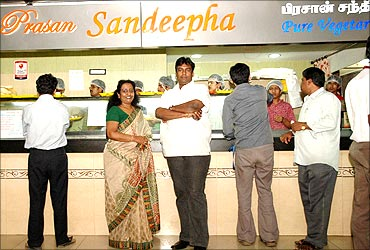 Patricia with her son Praveen in front of the Sandeepha restaurant.