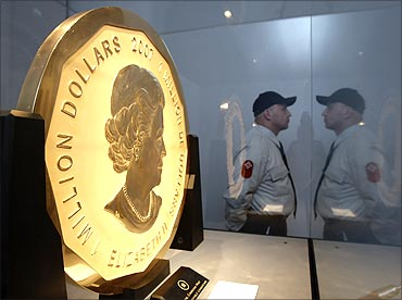 A security guard is reflected as he watches over the world's largest gold coin.