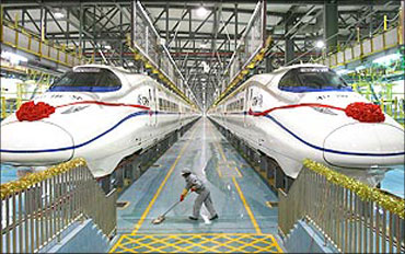 A labourer cleans the floor beside a China Railway High-speed (CRH) train preparing for the operation ce