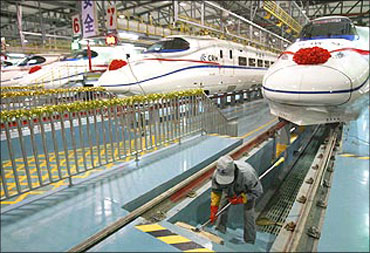 A labourer cleans the stairs beside a China Railway High-speed (CRH) train.