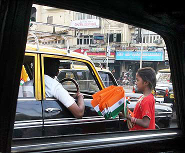 A girl sells flags at a traffic signal.