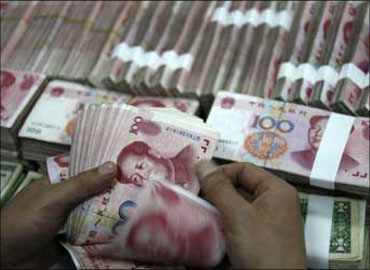 A Chinese bank teller counts currency.