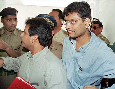Ketan Parekh (R) is escorted into a courtroom by Central Bureau of Investigation officers in Mumbai in March 2001.