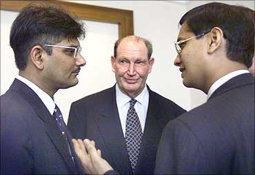 Australia's tycoon Kerry Packer (C) watches business partners Ketan Parekh (L) and Vinay Maloo (R) discuss a point during a news conference in Mumbai in March 2000.
