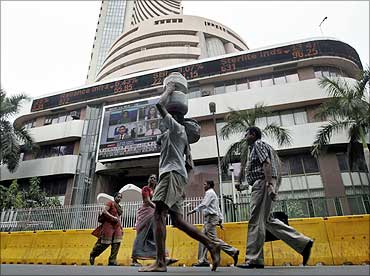 Commuters walk past the Bombay Stock Exchange building in Mumbai.
