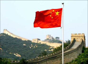 A Chinese flag flutters against the backdrop of the Great Wall of China.