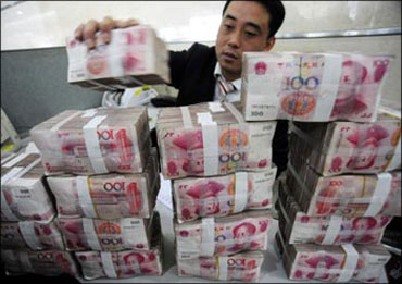 A Chinese bank employee placing currency notes on the bank counter.