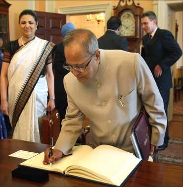 Finance Minister Pranab Mukherjee sigs the visitors book at the US State department, as Ambassador Meera Shankar looks on.