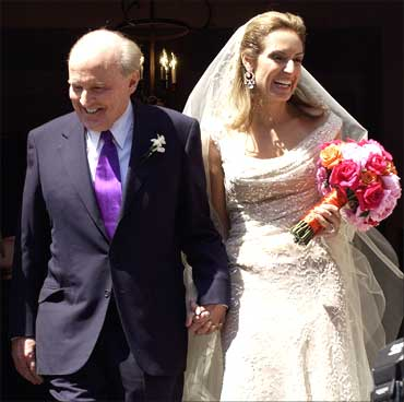 Jack Welch (L), walks down the steps of Park Street Church with Suzy Wetlaufer after their wedding in Boston, Massachusetts, April 24, 2004.