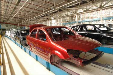 Shells of cars come out of the paint shop, all painted in shining bright colours.