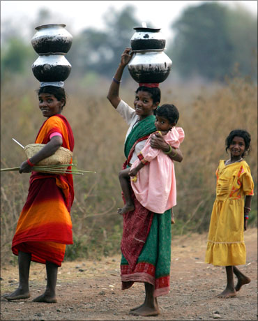 Village women walk barefoot to fetch drinking water in central Chhattisgarh.