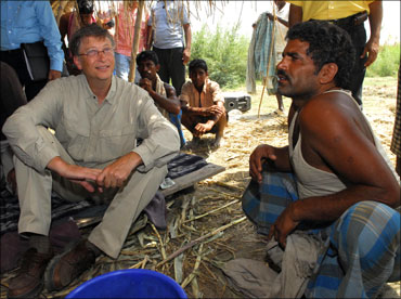 Microsoft co-founder Bill Gates (left) interacts with a villager in Aulali village, in Khagaria dist