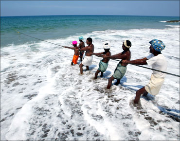 Indian fishermen pull in their catch in Kovalam Beach, near Trivandrum.