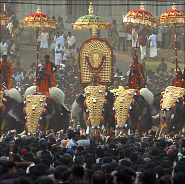 People attend a procession of decorated elephants during Trichur Pooram festival at Trichur in Ker