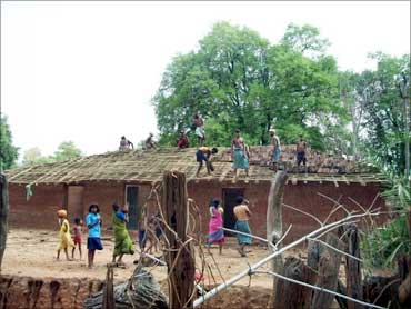 Villagers build a house.