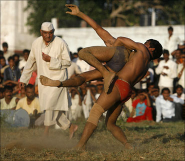 Indian wrestlers grapple with each other at an exhibition match.