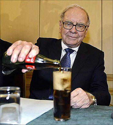 Warren Buffett fills a glass with Coke during a news conference in Madrid.
