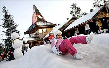 A child slides on snow in front of the Santa Claus' Office in Santa Claus' Village.