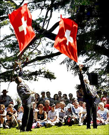 Traditionally dressed men take part in flag tossing during Switzerland's holiday celebrations.