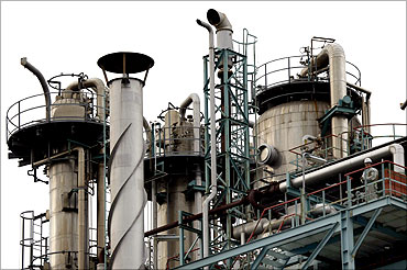 A worker stands next to the chimneys of an oil factory at Keihin industrial area in Kawasaki.