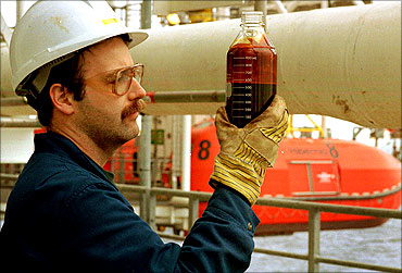 An oil rig worker checks a sample of the first crude oil to come out of Hibernia offshore resovoir.
