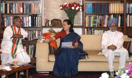 Sonia Gandhi (C) speaks with Finance Minister Pranab Mukherjee (L) as India's Prime Minister-elect Manmohan Singh watches.