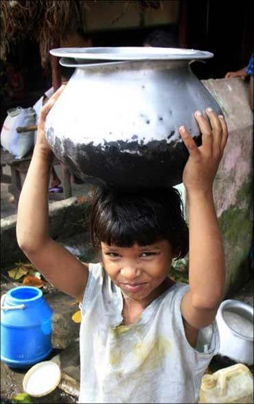 A homeless girl carries a pot o