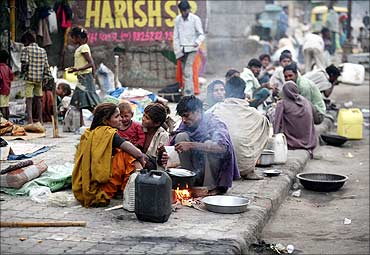 Homeless people prepare their food on a roadside in Ahmedabad.