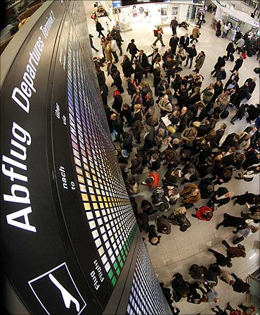 Passengers stand under a flight information display board at Munich Airport.