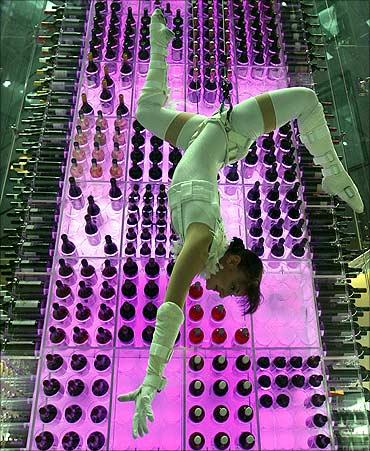 A so-called wine angel poses as she is suspended by steel ropes at a hotel in Zurich Airport.