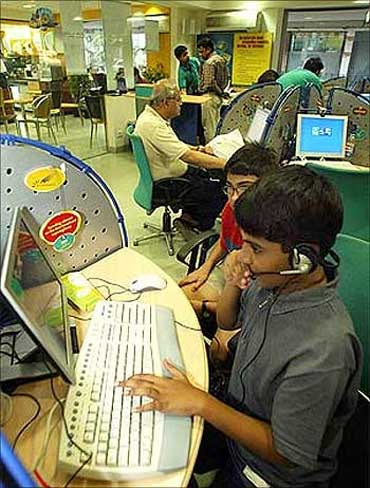 Children play computer games at an Internet cafe by run by Reliance Infocomm in Kolkata.