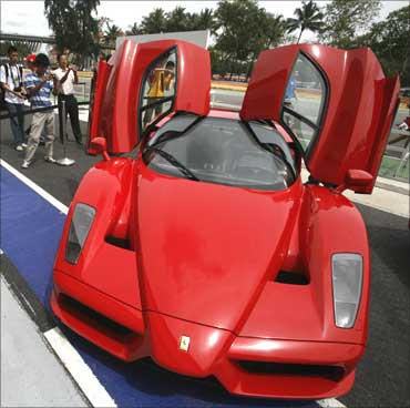 Visitors look at a Ferrari Enzo during a display of luxury cars in Singapore.