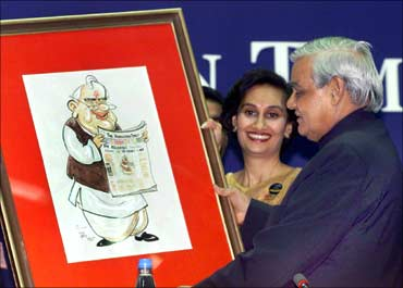 Atal Behari Vajpayee (R) smiles as he looks at his caricature presented to him by Shobhana Bhartia.