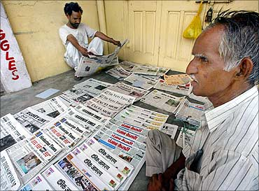 A newspaper vendor waits for customers on a street in Jammu.